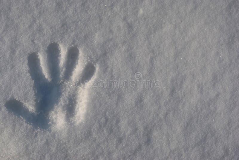 A impressão das mãos do ` s das crianças na neve branca fotografia de stock