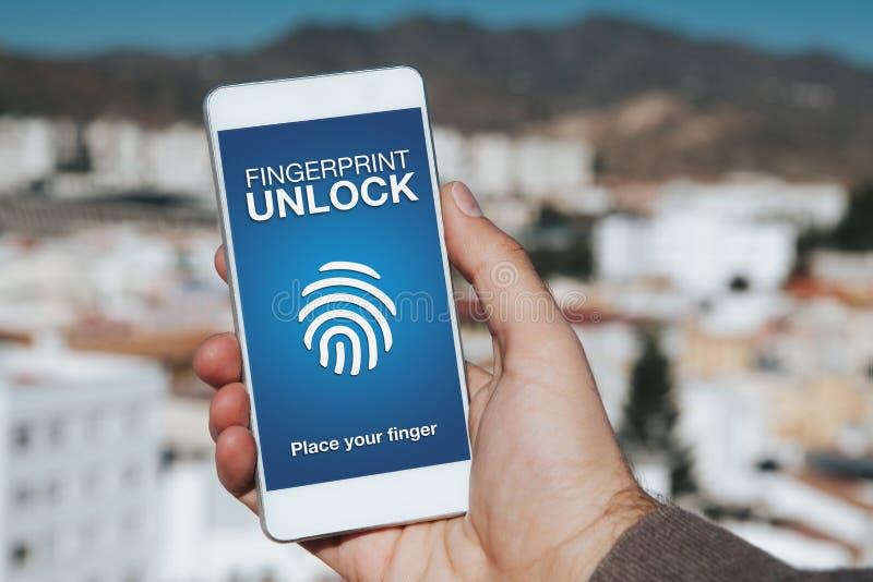 A impressão digital destrava a notificação em uma tela do telefone celular Mão do homem que guarda o telefone com fundo da cidade foto de stock royalty free