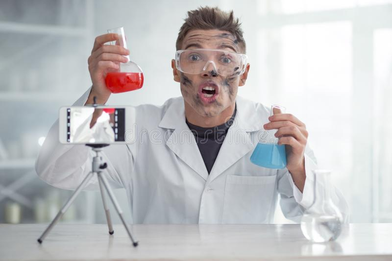 Impressed blogger having unexpected results after experiment. It is amazing. Handsome impressed dirty fair-haired young blogger and wearing uniform and holding stock image