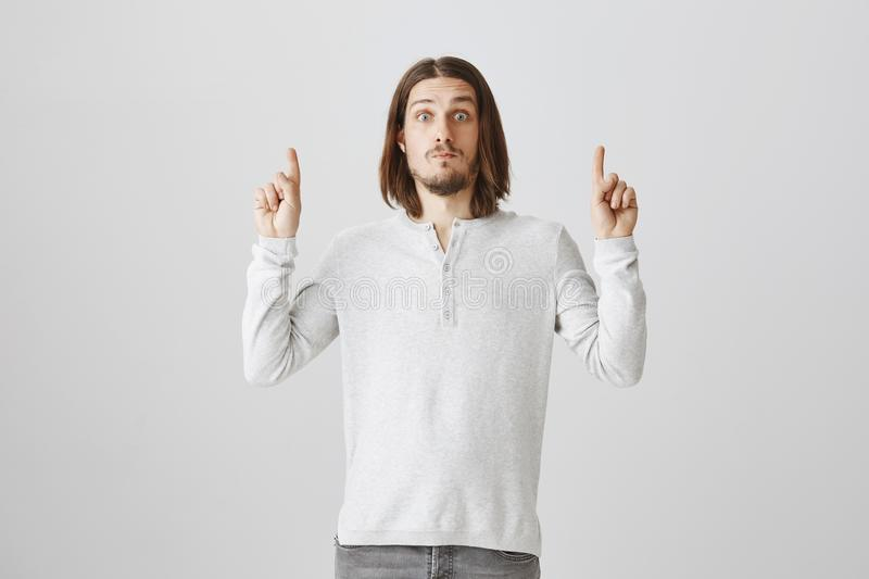 Impressed cute guy cannot believe his eyes. Portrait of handsome adult male model with beard and long hair pointing stock images