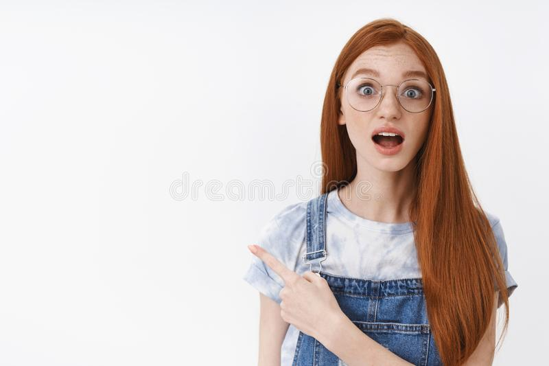 Impressed cute redhead girl with long hair open mouth astonished look camera amused pointing upper left corner. Questioned gaze you, asking question about royalty free stock photo