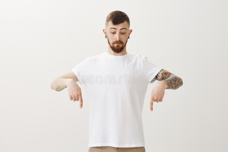 Impressed handsome bearded adult guy with tattoos, pointing and looking down with surprised and curious expression stock photo