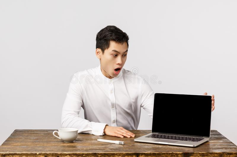 Impressed, shocked and astonished young chinese man in office, manager sitting table looking laptop screen, showing stock images