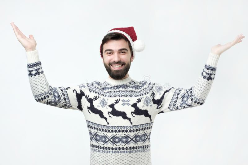 Hispanic man in sweater and christmas hat standing raising hands in amazement stock photography