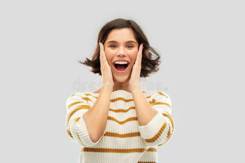 Impressed woman in pullover holding to her face. Emotion, expression and people concept - happy impressed young woman in striped pullover holding to her face royalty free stock image