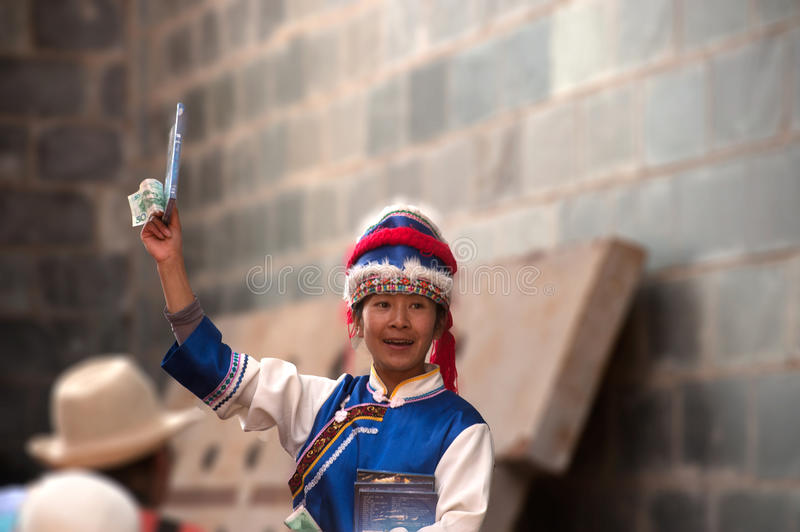 Impression Lijiang is traditional dance in China. LIJIANG,CHINA-MARCH 16 : Actors participate standing sell a CD Impression Lijiang on March 16,2014,at Yunnan stock image