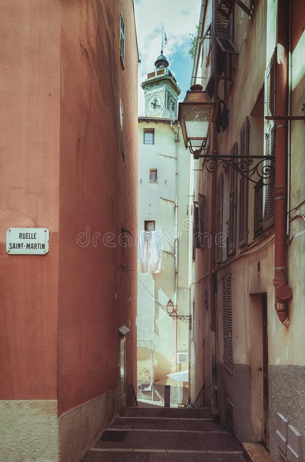 Impression of a narrow street in the old center of Nice with the steeple of La Tour Saint Francois in the background. Impression of a narrow street in the old royalty free stock images