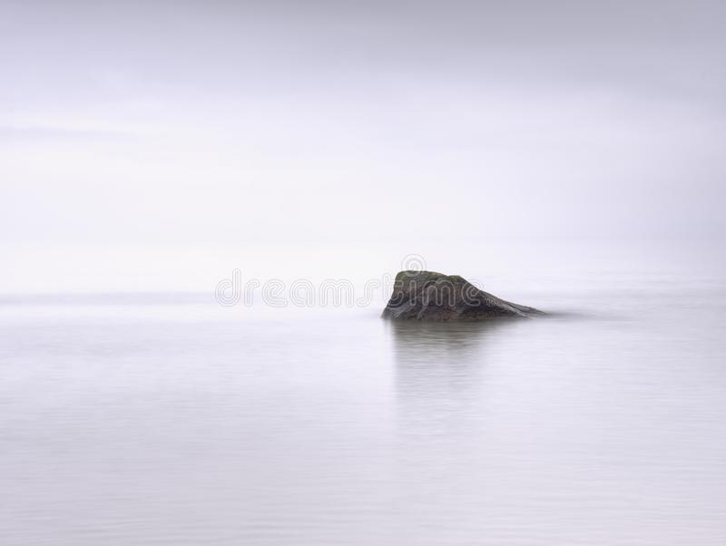 Impressive atmosphere of evening sea. Peaceful sea level with stones royalty free stock photography