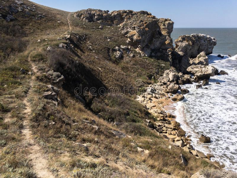 Impressive Crimean landscape. Narrow path along high cliffs over empty sandy beach and waves at sea. Copy space royalty free stock photos