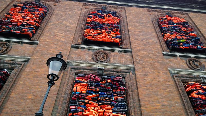 An impressive exhibition on the waterfront in Copenhagen, Chinese artist Ai Weiwei. Bright life jackets placed in the Windows stock images