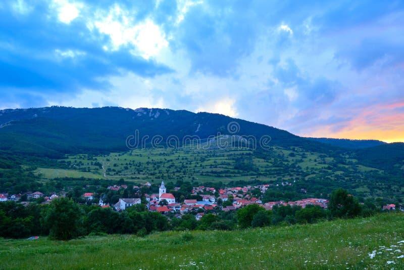 Impressive sunset with orange setting sun and blue/purple clouds, over Rimetea village, Alba county, Transylvania, Romania stock photography