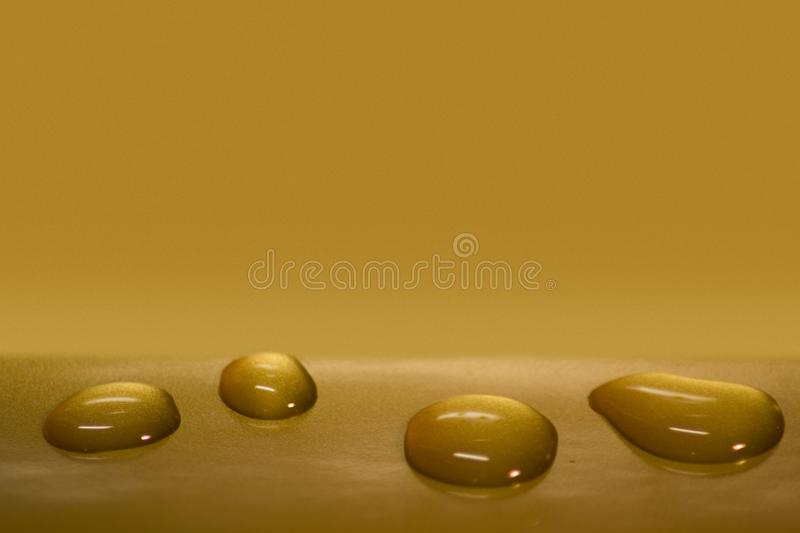 Impressive water drops on the gold background stock image