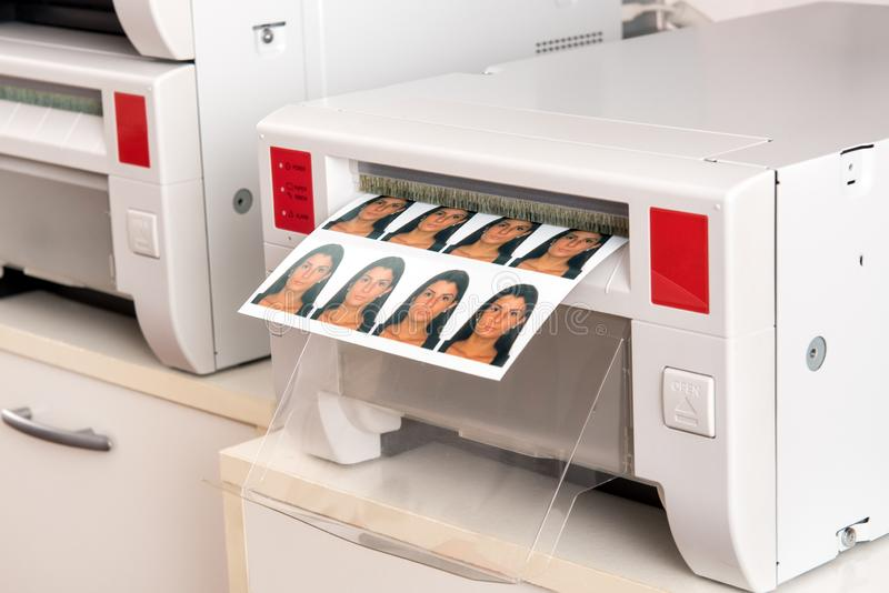 Imprimindo fotos do passaporte de uma mulher em uma impressora foto de stock