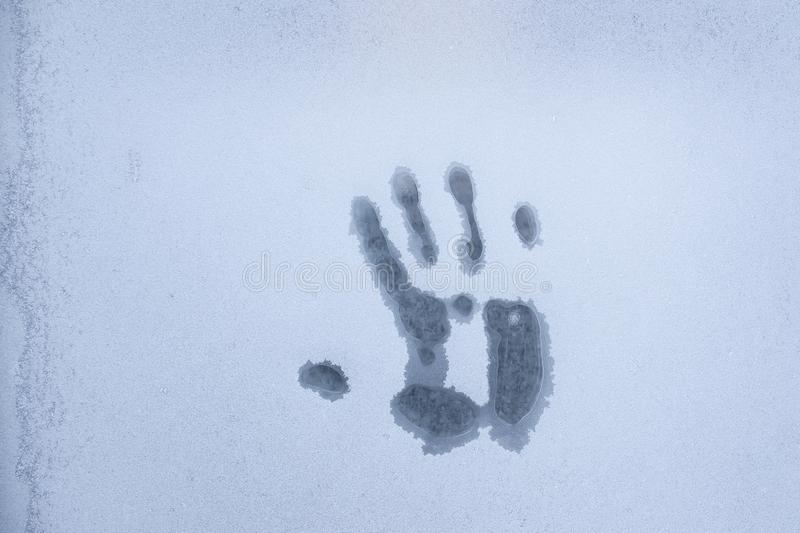 Imprint of a human palm on a frozen window glass inspires fear and horror royalty free stock image