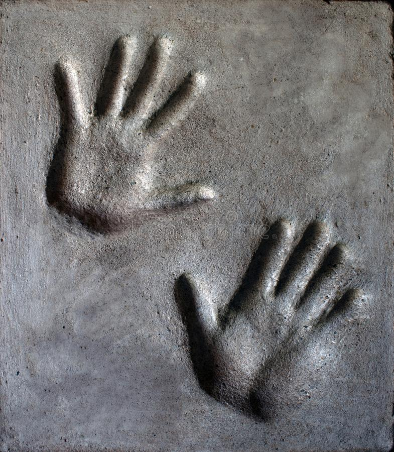 Imprint of mans and womans hand in mortar stock images