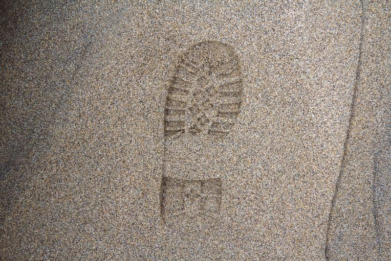 Imprint of the shoe on mud with copy space, Footprint in the dirt, Foot step on sand, background texture. Top view. royalty free stock photos