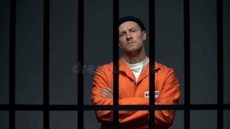 Imprisoned dangerous male criminal crossing hands on chest, looking directly stock photo