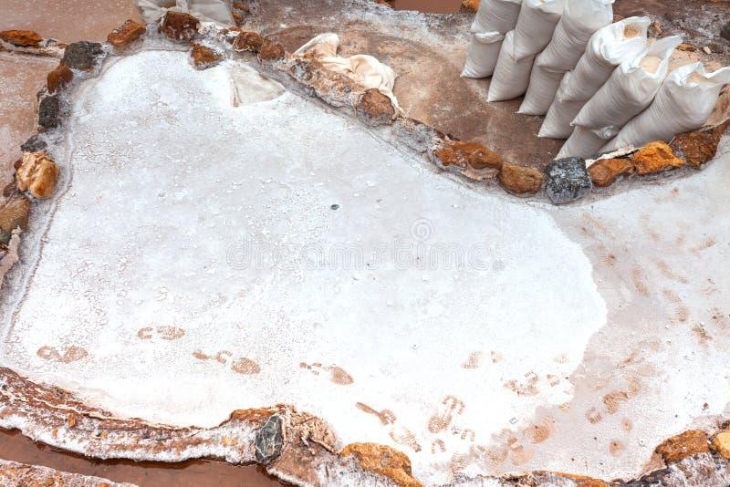 Impronte sugli stagni di evaporazione, sacchi di sale raccolto nelle vicinanze Salineras a Maras, Perù, America Latina immagini stock libere da diritti