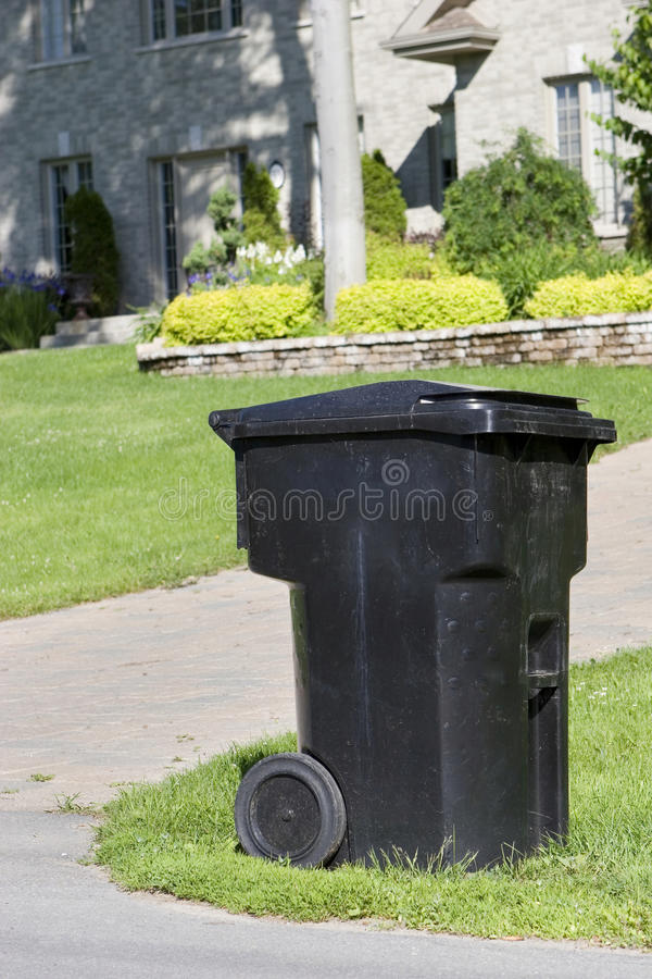 Improperly positioned wheeled garbage can curbside.  stock images