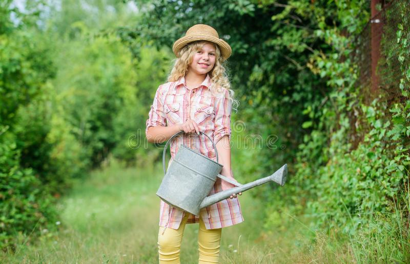 Improve irrigation timing. Optimize water use. Watering plants in garden. Girl child hold watering can. Spring gardening royalty free stock image