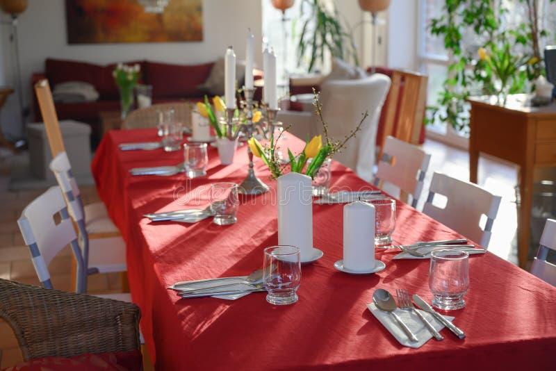 Improviserad äta middag tabell för många gäster med den röda bordduken och garnering i vardagsrummet royaltyfri bild