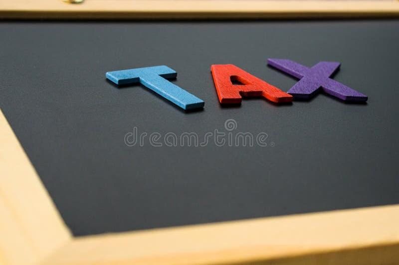 IMPUESTO del alfabeto en el tablero negro, concepto de las finanzas foto de archivo