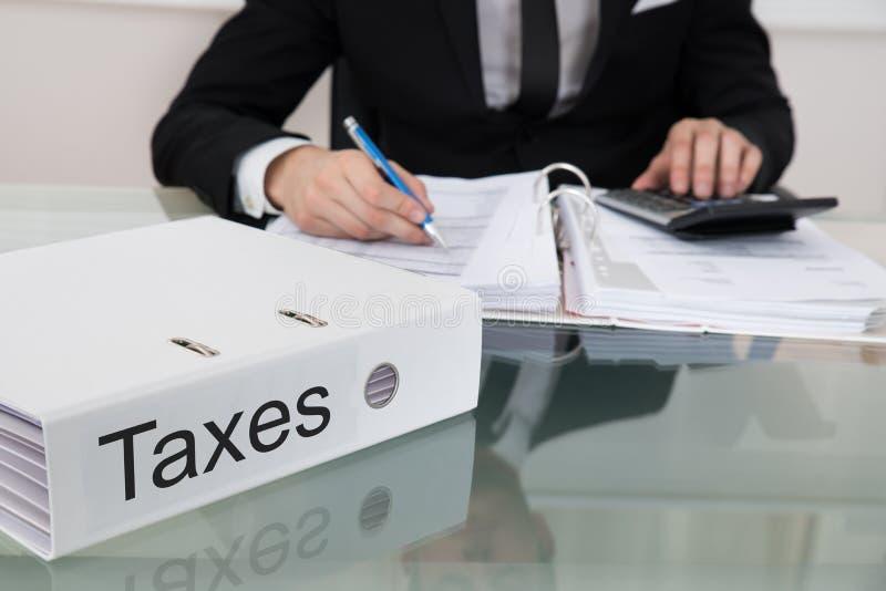 Impuestos calculadores del hombre de negocios imagen de archivo