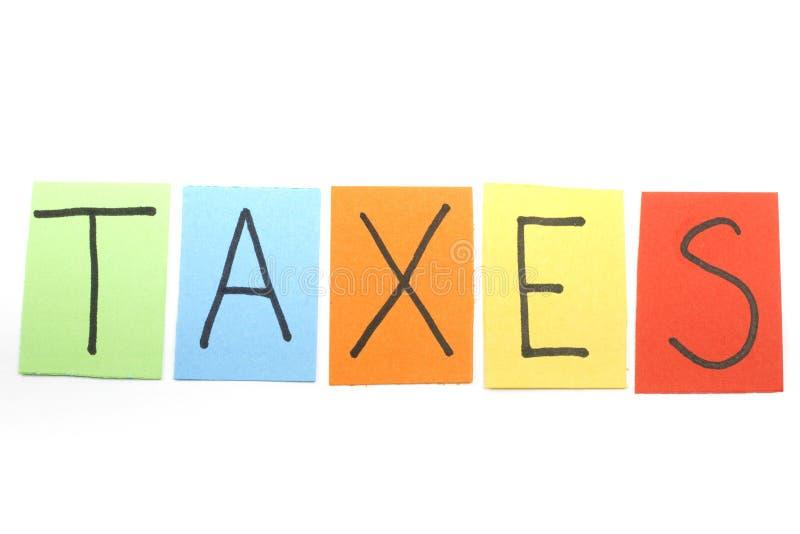 Impuestos escritos en letras coloridas imagen de archivo