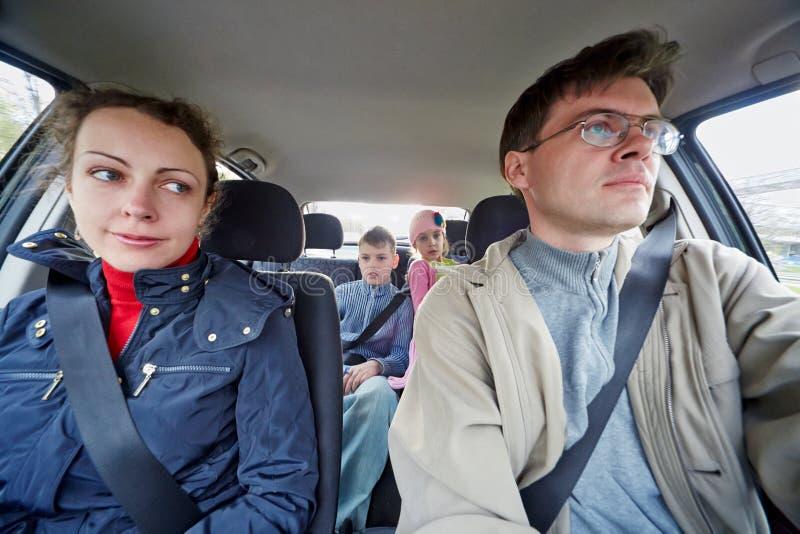 Impulsión de la familia de cuatro miembros en coche foto de archivo libre de regalías