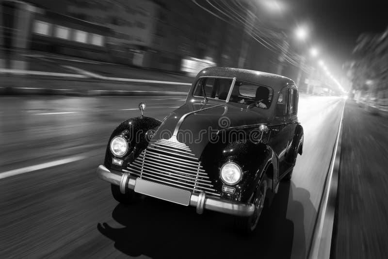 Impulsión rápida del coche retro viejo en el camino de ciudad del asfalto en la noche fotografía de archivo