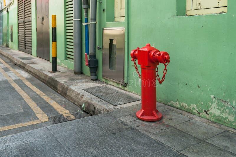 Impulsionador vermelho da boca de incêndio, boca de incêndio de fogo na rua foto de stock