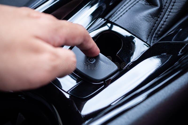 Impulso da mão no botão eletrônico do handbrake no carro moderno imagens de stock