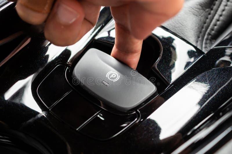 Impulso da mão no botão eletrônico do handbrake no carro moderno luxuoso imagem de stock