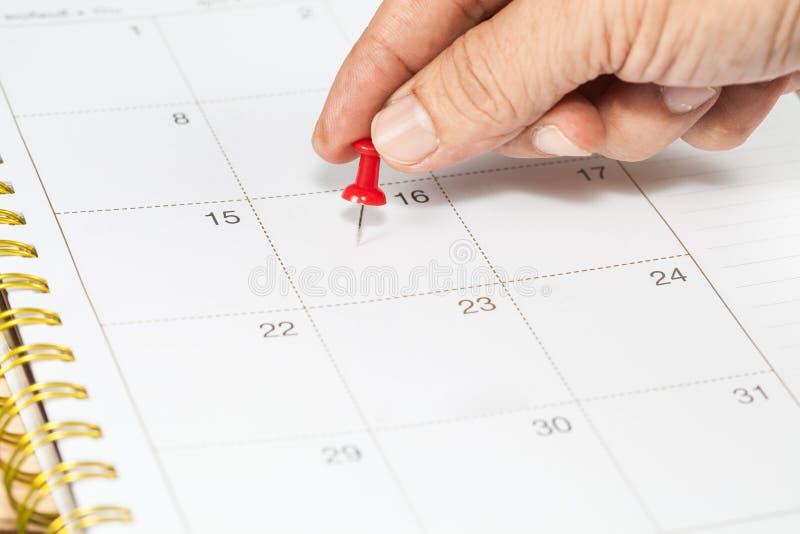 Impulso da mão uma marca do pino no calendário fotos de stock royalty free
