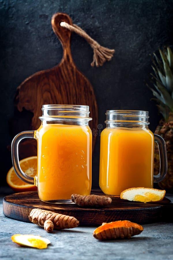 Impulso inmune, smoothie inflamatorio anti con la naranja, piña, cúrcuma Bebida del jugo de la mañana del Detox fotografía de archivo