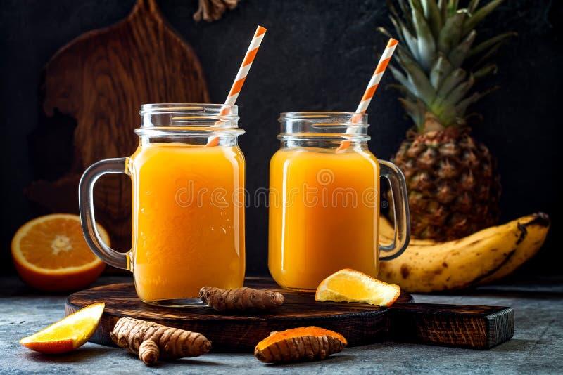 Impulso inmune, smoothie inflamatorio anti con la naranja, piña, cúrcuma Bebida del jugo de la mañana del Detox fotografía de archivo libre de regalías