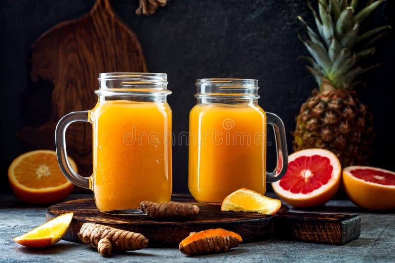 Impulso inmune, smoothie inflamatorio anti con la naranja, piña, cúrcuma Bebida del jugo de la mañana del Detox imagenes de archivo