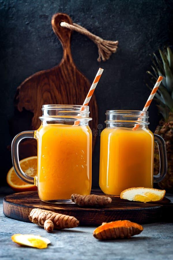 Impulso inmune, smoothie inflamatorio anti con la naranja, piña, cúrcuma Bebida del jugo de la mañana del Detox fotos de archivo