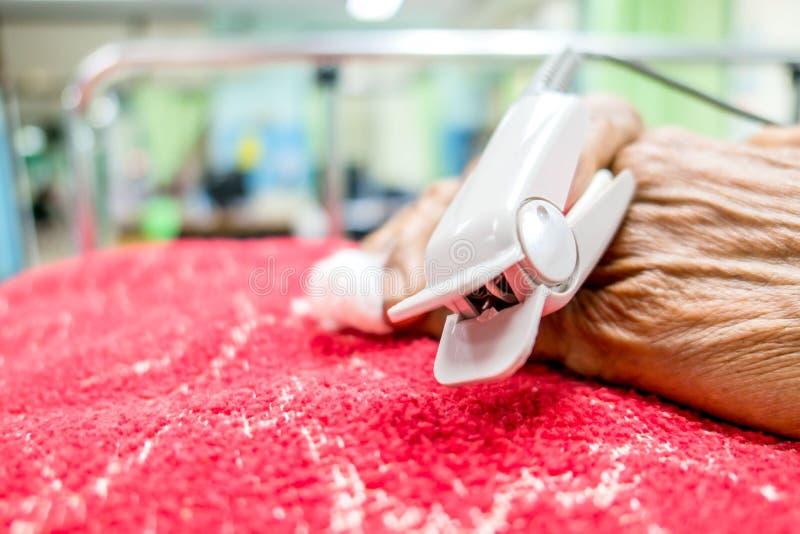 Impulsoximeter in een mannelijke geduldige vingertop van ` s in het ziekenhuis stock afbeelding