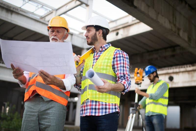 Inżynier, brygadier i pracownik dyskutuje w budynek budowie, zdjęcia stock