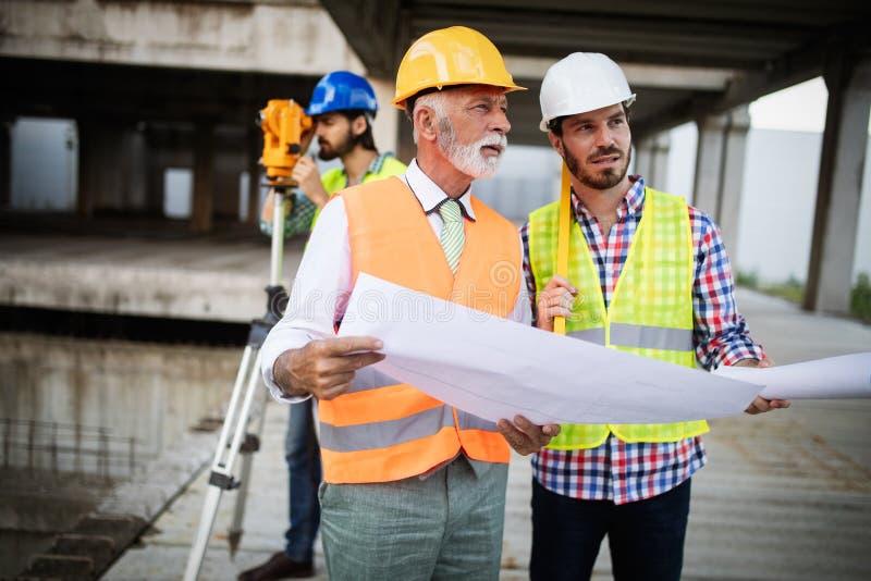 Inżynier, brygadier i pracownik dyskutuje w budynek budowie, obraz royalty free