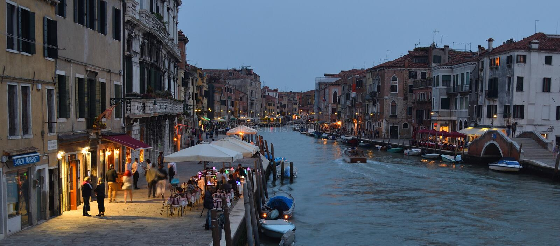 Início da noite do canal de Cannaregio com restaurantes e as barras iluminados Veneza imagens de stock royalty free