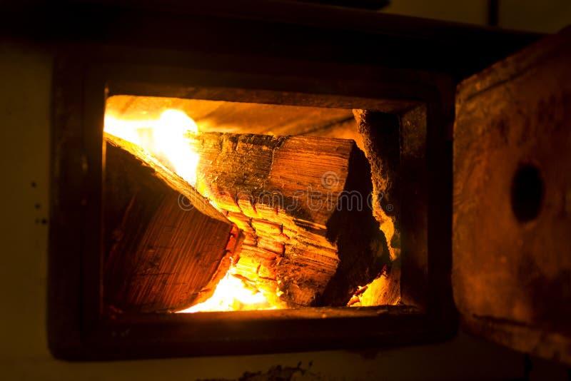 Início de uma sessão ardente o fogão velho, log do burning do perigo imagens de stock