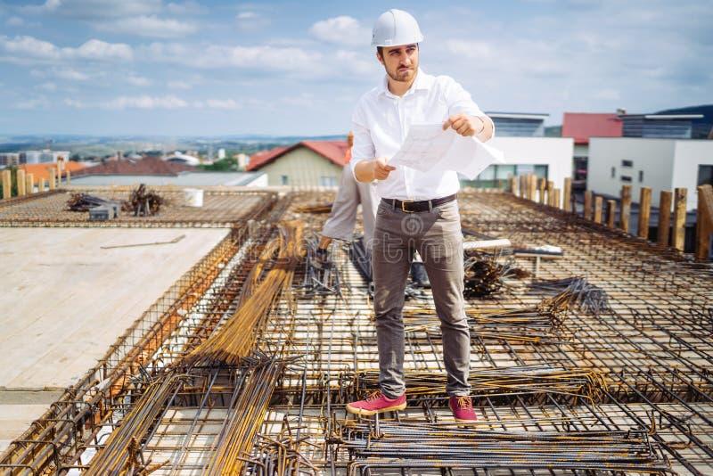 Inżynier, architekt jest ubranym hardhat i ochronną przekładnię dogląda budowę fotografia royalty free