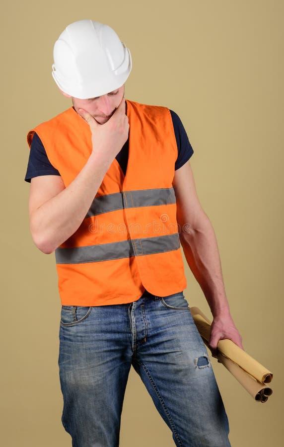 Inżynier, architekt, robotnik, budowniczy na rozważnej twarzy trzyma starych projekty w ręce Mężczyzna, brygadier w hełmie, ciężk fotografia royalty free