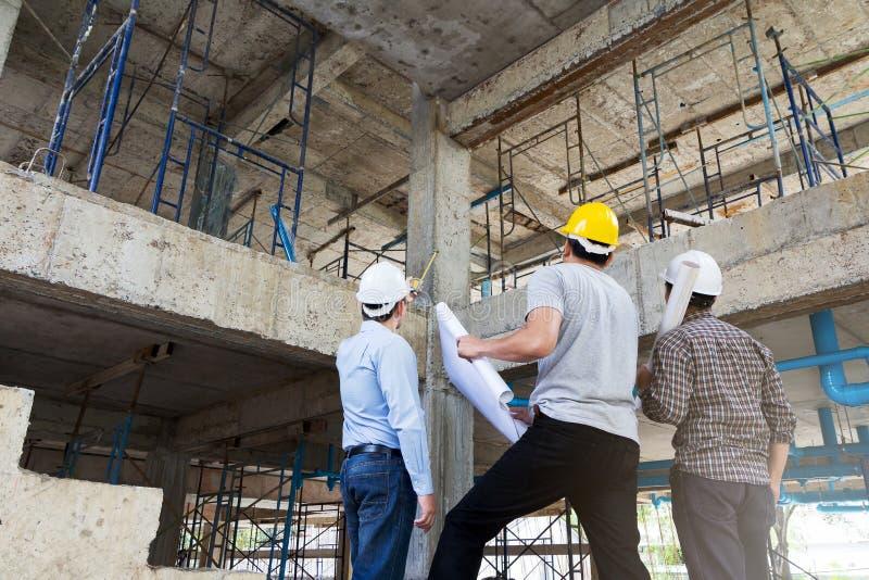 Inżynier, brygadier i pracownik dyskutuje w budowie, zdjęcie royalty free
