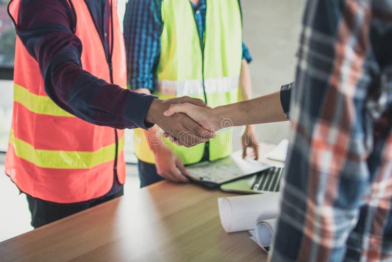 inżynier i pracownik trząść ręki przed heblować const i opowiadać fotografia royalty free