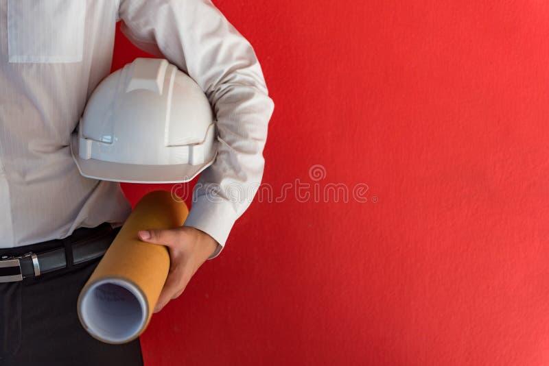 Inżynier lub architekt trzyma zbawczego hełm i rysunek zdjęcia stock