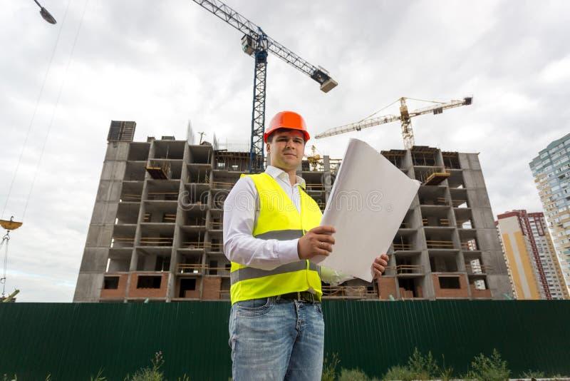 Inżynier na placu budowy z projektami zdjęcie royalty free