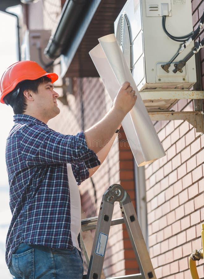 Inżynier patrzeje w planie klimatyzacja w hardhat zdjęcia royalty free